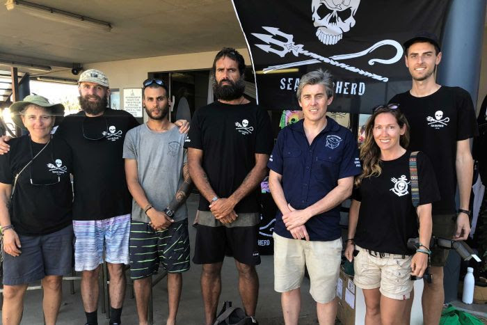Members of conservation group Sea Shepherd standing in front of their iconic flag at Mackay Harbour.