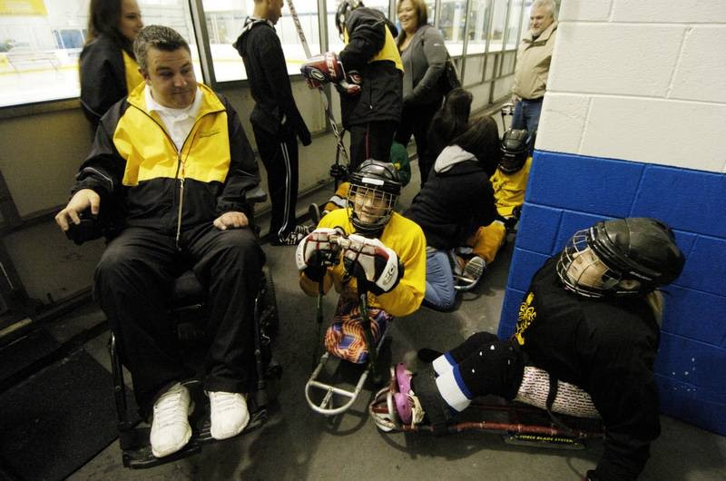 Chicago Hornets General Manager J.J. O'Connor, left, says fundraising sled hockey games help supply equipment and ice time for players with disabilities.