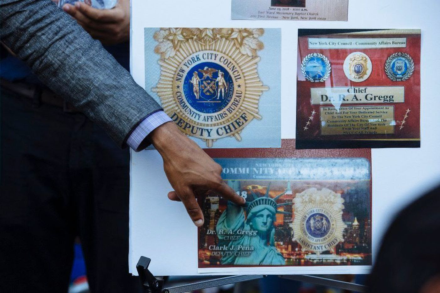 City Councilman Ritchie Torres points to images of badges created for a fake city department used for fraudulent fund-raising for Feliz-Guzman in the Bronx.