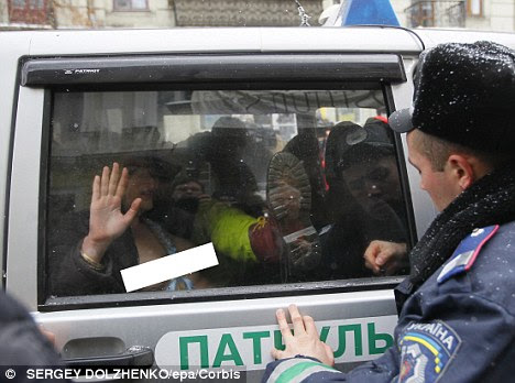 The authorities detain several protesters who are held in a police vehicle