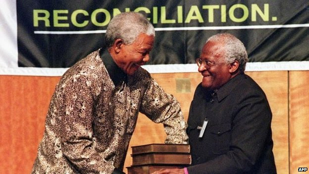 Then-South African President Nelson Mandela (L) receives a five volumes of Truth and Reconciliation Commission final report from Archbishop Desmond Tutu, in Pretoria 29 October 1998