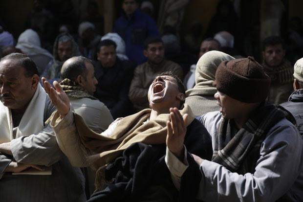 Egípcios choram nesta segunda-feira (16) a morte de cristãos coptas que foram decapitados pelo Estado Islâmico na Líbia (Foto: Hassan Ammar/AP)