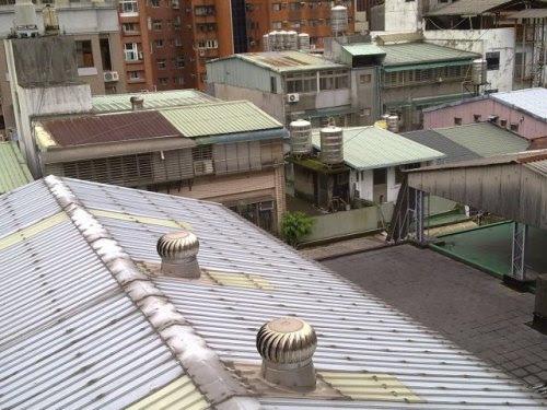 Taipei: All that Jazz - View from the rear window (photo: Jan. 5, 2013)台北:滅茶苦茶 - 裏窓からの眺め表通りは恵まれた容積率で高層アパートが、それらの建物に囲まれた路地裏は四五階。そして屋上屋を重ねた風景がこれ。こちらでいう「鉄皮屋」、トタン板で囲まれた増築建物。そのほとんどは違法建築。手前のベトナム換気扇を屋根に取り付けた建物、一昨年にあっという間に出来上がり、トタン屋根の上に高架水槽を設けていたものの、どこからか通報があって、悪く言えば密告があり撤去されてしまった。水槽は仕方なくトタン屋根の下へと移動する羽目に。増築部分のほとんどに人様が住まわっておいでになる。夏場は相当な暑さだろうに…。