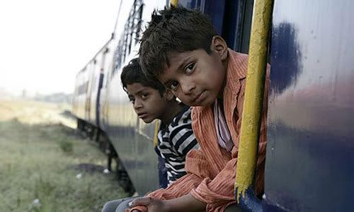 Young Jamal (Ayush Mahesh Khedekar) and his brother Salim (Azharuddin Mohammed Ismail) hitch a ride in SLUMDOG MILLIONAIRE.