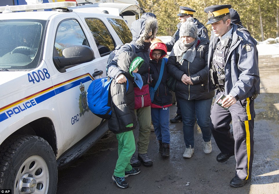 Polls show Canadians are split over whether Canada should be accepting more or fewer refugees. But even Liberal legislators are starting to hear from constituents concerned about the arrivals. A family talks with police on Monday near Hemmingford, Quebec