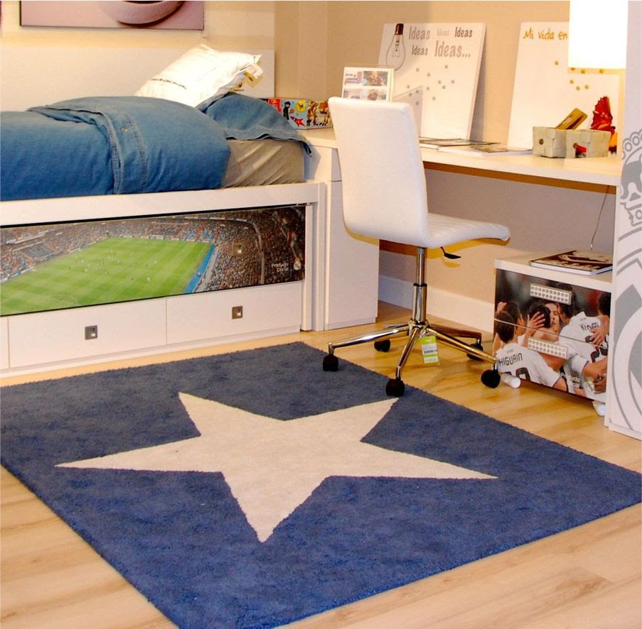 blue fury carpet with white star ornament in the center of carpet double layered bedding with under storage a desk with under shelf and a white movable chair wood finishing floor