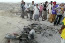 People gather around a motorcycle destroyed in a drone strike near al-Sheher town of Yemen's eastern region of Hadramout