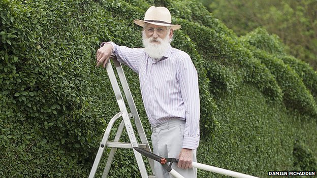 John Brooker standing with hedge clippers on a stepladder