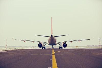 Pista de pouso e decolagem com avião branco parado.