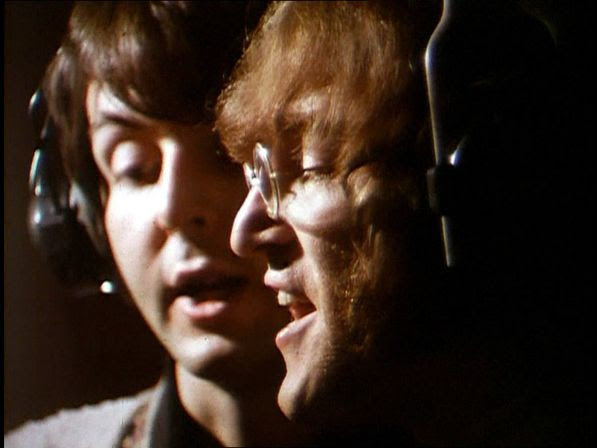 Beatles members John Lennon and Paul McCartney sing their harmonizing vocal lines in the Abbey Road Studios in London, England, February 11, 1968, during a recording session.