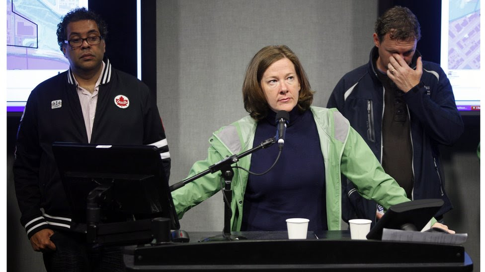 Alberta Premier Alison Redford, centre, addresses the media as Calgary Mayor Naheed Nenshi, left, and Alberta Municipal Affairs Minister Doug Griffiths look on during a news conference in Calgary, Alberta, Canada Friday, June 21, 2013.