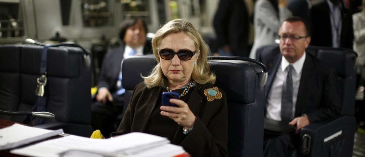 Hillary Clinton using her personal BlackBerry during trip to Libya. (REUTERS/Kevin Lamarque)