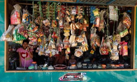 MDG : Burma : A vendor talks on phone in her shop in Dala, Yangon, Myanmar
