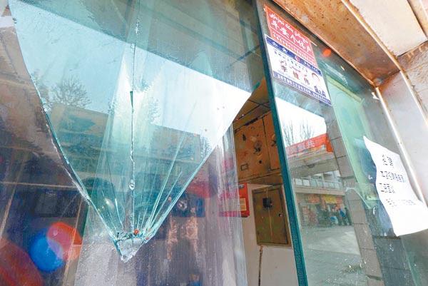 幸福路步行街一間被砸店舖的玻璃仍留有血漬。(中新社圖片)