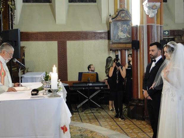 Falsos noivos ficam diante do padre na mira da fotógrafa que viria a se tornar a verdadeira noiva da cerimônia (Foto: Thais Pimentel/G1 MG)