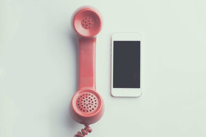 The pink receiver of an old phone alongside an iPhone on a white table..