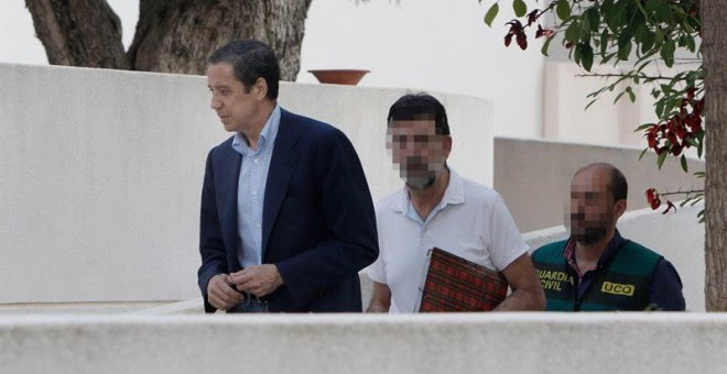 El expresidente de la Generalitat Valenciana y exministro de Trabajo, Eduardo Zaplana, a su llegada a su chalé de Benidorm (Alicante) acompañado por agentes de la UCO de la Guardia Civil. - EFE