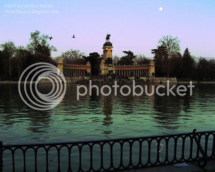 Vista atardeciendo del estanque y del monumento a Alfonso XII en el Parque del Buen Retiro de Madrid con la luna y dos patos volando