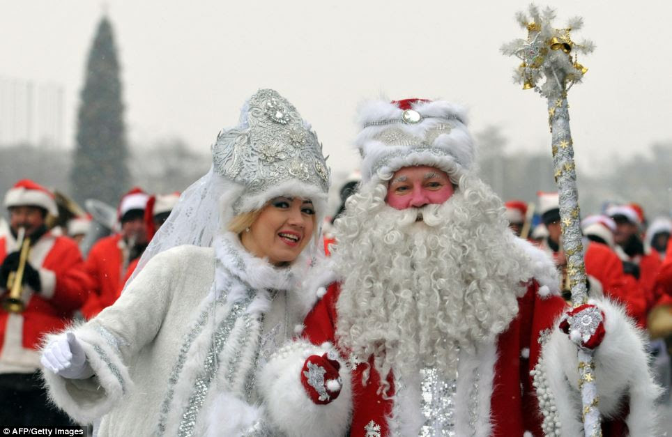 Actors dressed as the Russian Ded Moroz (Grandfather Frost), right, and his companion Snegurochka (Snow Maiden), left, take part a New Year parade in the Kyrgyzstan's capital Bishkek