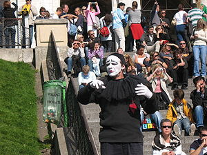 Parisian mime working for tips entertaining crowd.
