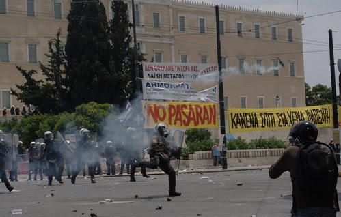 Greek riot police throwing tear gas cannister at protesters. Syntagma Square, Athens
