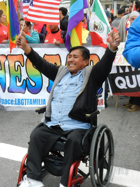 1immigrant marcher in chair smiling!.jpg