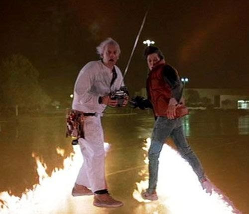 Outside the Twin Pines Mall, Doc Brown and Marty McFly stare at the after-effects of the DeLorean traveling back in time in BACK TO THE FUTURE.