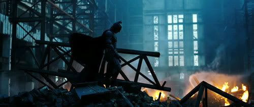 Batman stands amid a pile of wreckage.