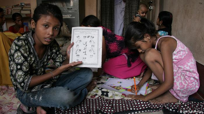 A child contributor of the brothel magazine Jugnu is showing the cover of a recent issue, sitting at the office of Parcham. Some other child contributors are also caught in the frame. (Photo: Aziz Rahman / DW)