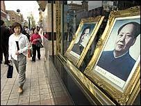 Mujer china pasando frente a un retrato de Mao