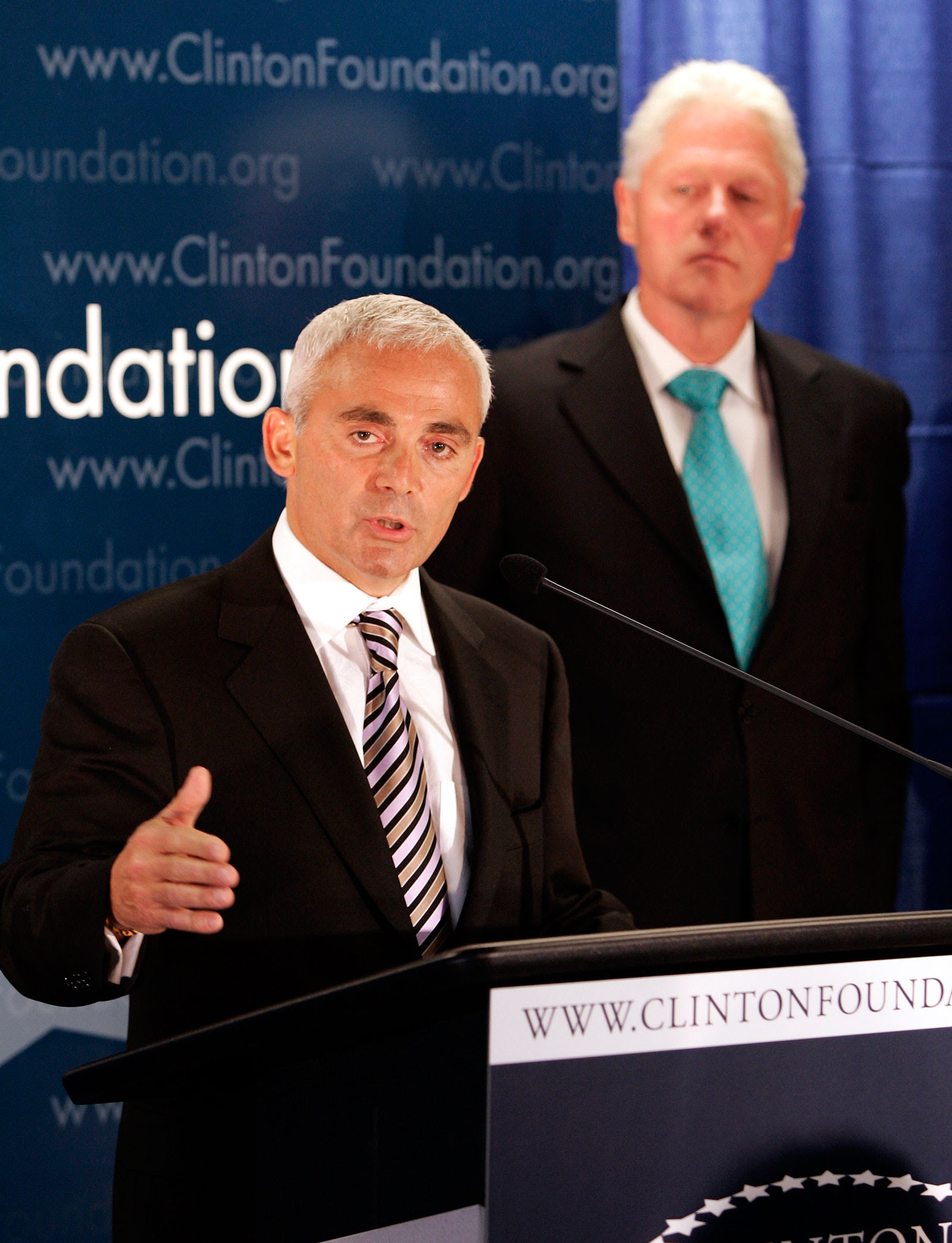 Frank Giustra speaks as former President Bill Clinton looks on during a press conference announcing the Clinton Giustra Sustainable Growth Initiative, New York, June 21, 2007