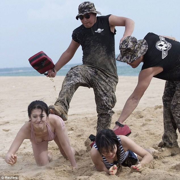 Best foot forward: Two bikini-clad trainees are kicked and hit with pads as they crawl on the beach during a bodyguard training session in Sanya, China
