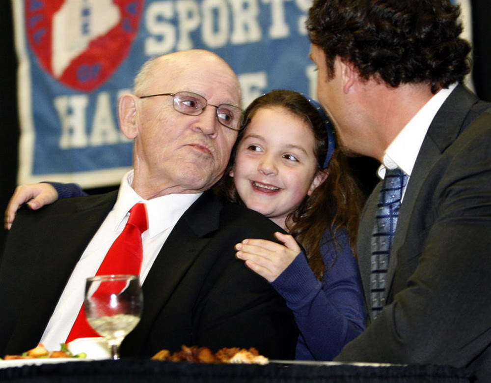 "Maine Sports Hall of Fame inductee Harold ""Tank"" Violette receives a hug from his granddaughter, Allison Hegarty, during the Maine Sports Hall of Fame awards banquet on May 22, 2011, at the Augusta Civic Center. Violette died Tuesday"