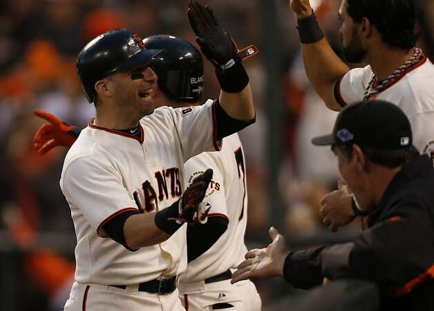 Giants' second baseman Marco Scutaro gets a high five from Angel Pagan after scoring in the 3rd inning during game 7 of the NLCS at AT&T Park on Monday, Oct. 22, 2012 in San Francisco, Calif. Photo: Michael Macor, The Chronicle / SF