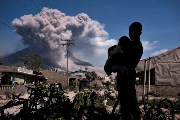 A boy carries his brother as the Mount Sinabung spews pyroclastic smoke at Sibintun village on February 7, 2014 in Karo District, North Sumatra, Indonesia. The number of displaced people has increased to around 30,000 in Western Indonesia as Mount Sinabung continues to spew ash and smoke after a series of several eruptions since September. At least 16 people were killed in an eruption of Mount Sinabung on February 1, after residents were allowed to returned to their homes on January 31 by authorities who had said that activity was decreasing.