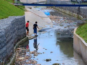 Imagem de 2011 mostra crianças da comunidade São Nicolau, em São Paulo, em área onde esgoto passava a céu aberto. Área sofria com a ausência da coleta e tratamento de esgotos (Foto: Divulgação/Instituto Trata Brasil)