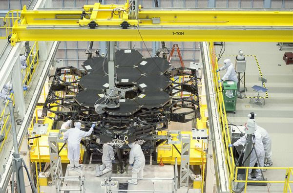 Engineers install the ninth of 18 mirror segments onto the James Webb Space Telescope's backplane at NASA's Goddard Space Flight Center in Greenbelt, Maryland.