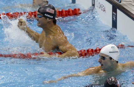 United States' Nathan Adrian, left, celebrates his gold medal win in the men's 100-meter freestyle swimming final at the Aquatics Centre in the Olympic Park during the 2012 Summer Olympics in London, Wednesday, Aug. 1, 2012. Australia's James Magnussen is seen to his right.(AP Photo/Lee Jin-man)