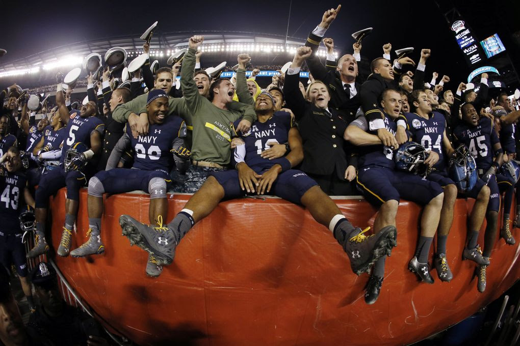 Navy quarterback Keenan Reynolds (19) celebrates with fellow Navy Midshipmen after their game against Army on Saturday in Philadelphia. (19) celebrates with fellow Navy Midshipmen after their game against Army on Saturday in Philadelphia. Navy won 21-17.  (Matt Slocum / AP)