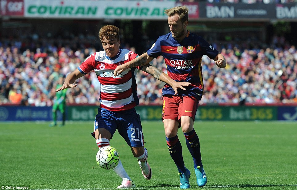 Granada's Adalberto Penaranda battles for the ball with Croatian midfielder Ivan Rakitic on a sunny day in the south of Spain