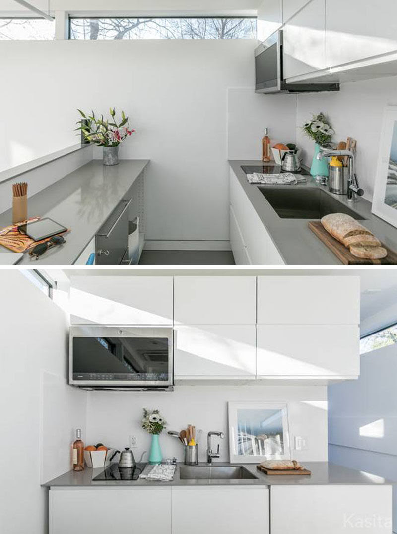 This small white and grey kitchen has a two burner induction cooktop and a convection microwave oven, as well as more storage and two counter spaces.
