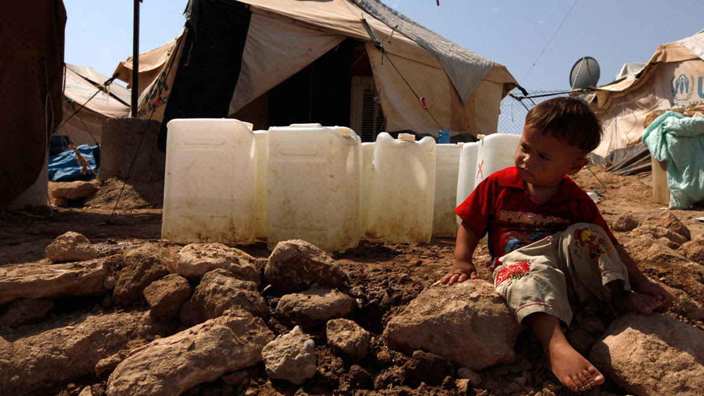 Campamento de refugiados: un niño descansa junto al agua potable