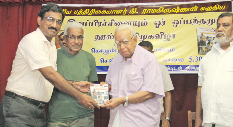 T. Ramakrishnan presents a copy of his book to Opposition Leader R. Sampanthan in Colombo recently.