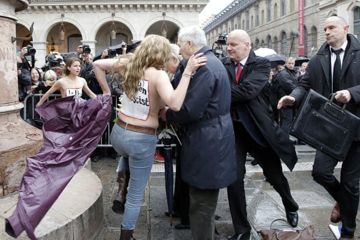 "<strong>Paris France</strong> Femen activists with ""Le Pen Top Fascist"" painted on their bodies appear as France s far-right National Front president Marine Le Pen places a wreath at Joan of Arc statue during its annual May Day march"
