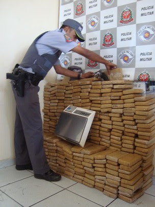Policial militar organiza pilha com tijolos de maconha (Foto: Adriane Souza/G1)
