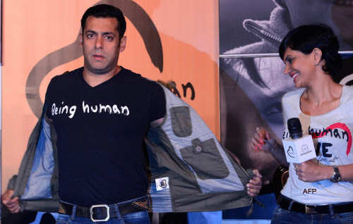 Actress Mandira Bedia (R) looks on as Bollywood film actor Salman Khan takes off his jacket during the launch of his 'Being Human' flagship clothing store in Mumbai on January 17, 2013.