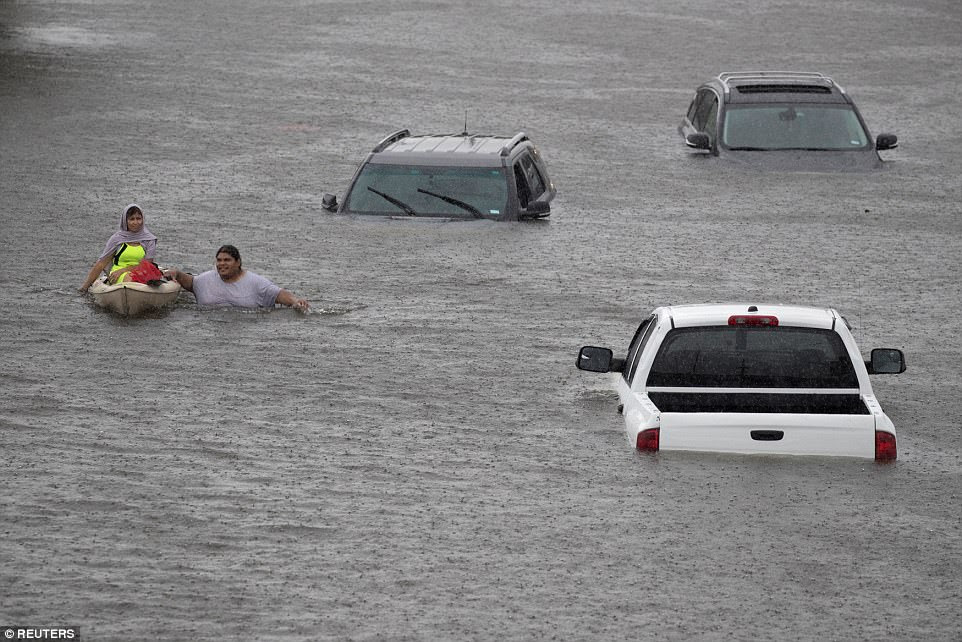 Jesus Rodriguez rescues Gloria Garcia after rain from Hurricane Harvey flooded Pearland, in the outskirts of Houston