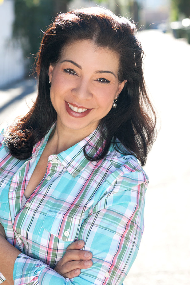 Carmen De La Paz smiles and looks at the camera while wearing a light blue plaid button down shirt