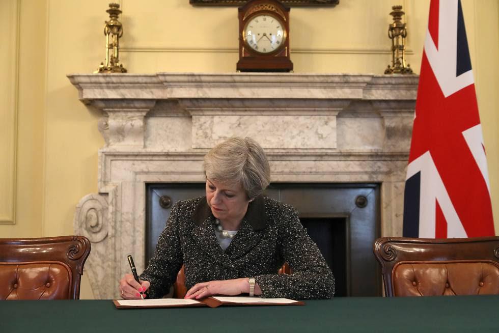 Theresa May firma la carta en la que activa el 'Brexit'.
