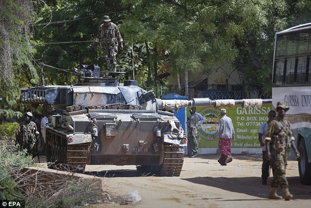 A Kenyan soldier takes cover as shots are fired in front of Garissa University College in Garissa town, located near the border with Somalia